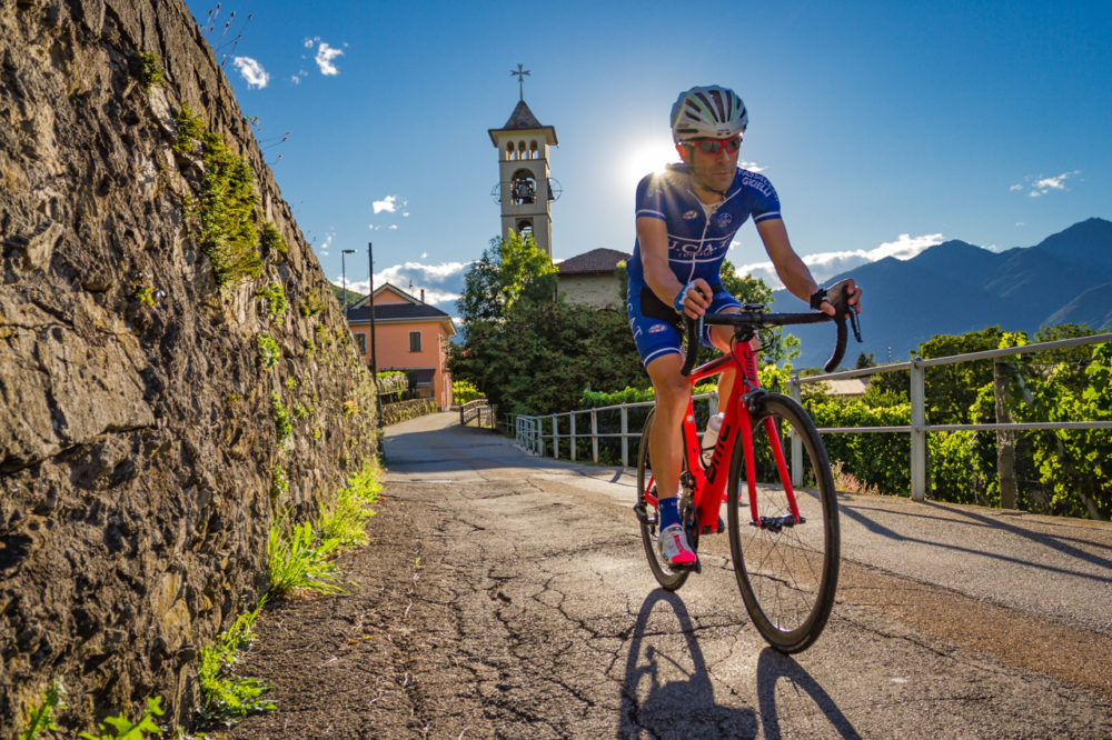 One male cyclist riding past a church in the Piano di Magadino in Ticino, Switzerland